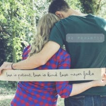 Couple holding a paper banner with love quote on